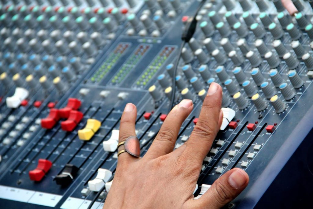 hand sliding a fader on a mixer