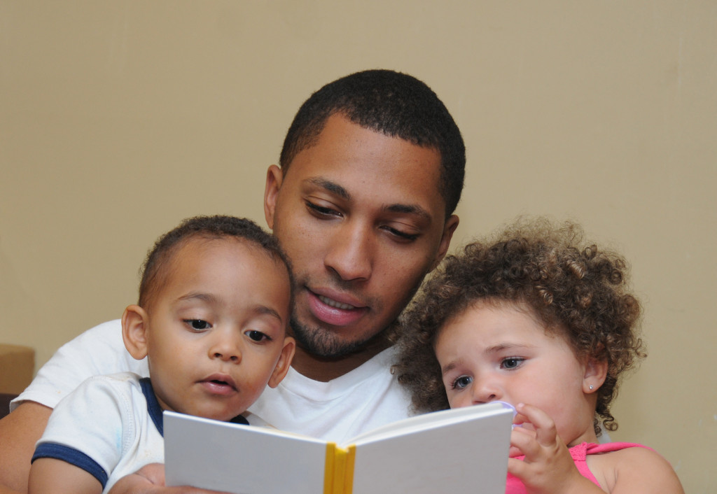 children reading book with father